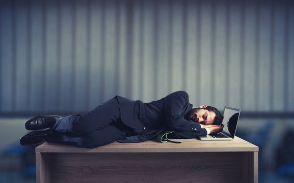 Businessman sleeping over a desk due to overwork