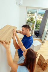 Closeup of a young man installing a shelf on a wall. Home decoration and renovation concept.