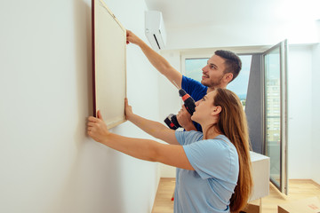 Young man with his girlfriend hangs the art picture on wall at home. Home decoration and renovation concept.