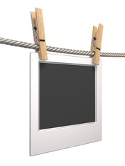 Clothes pin and blank photo paper hanging on rope side view 3D