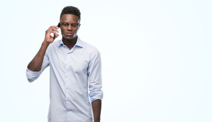 Young african american man using smartphone with a confident expression on smart face thinking serious