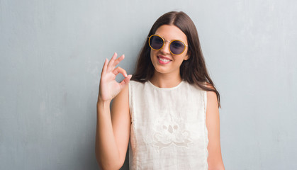 Young brunette woman over grunge grey wall wearing retro sunglasses doing ok sign with fingers, excellent symbol