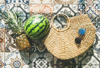 Summer lifestyle background. Flat-lay of summer fruit pineapple and watermelon, straw bag and sunglasses over colorful moroccan tile floor, top view, horizontal composition