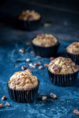 banana nut bread muffins with pecans on blue marble background