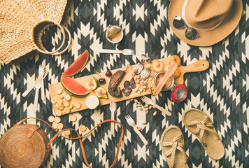 Aluminium Prints Picnic Summer picnic setting. Flat-lay of fresh fruit, smoked sausage, nuts, cheese, pate, cracker on board and woman straw accessories over linen blanket background, top view. Outdoor gathering or lunch
