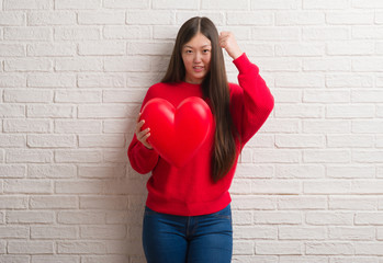 Young Chinese woman in love over brick wall holding red heart annoyed and frustrated shouting with anger, crazy and yelling with raised hand, anger concept