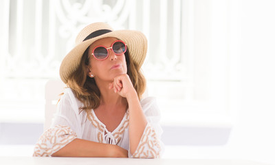 Middle age brunette woman sitting at the table serious face thinking about question, very confused idea