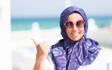 Middle age brunette arabian woman by the pool wearing sunglasses pointing and showing with thumb up to the side with happy face smiling