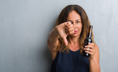 Middle age hispanic woman standing over grey grunge wall holding beer bottle with angry face, negative sign showing dislike with thumbs down, rejection concept
