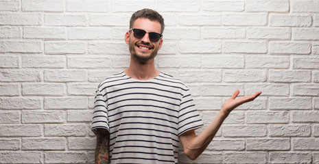 Young adult man wearing sunglasses standing over white brick wall smiling cheerful presenting and pointing with palm of hand looking at the camera.
