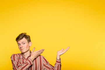 smiling young man pointing sideways with hands as if showing to smth. portrait of a guy on yellow background. copyspace for advertisement.