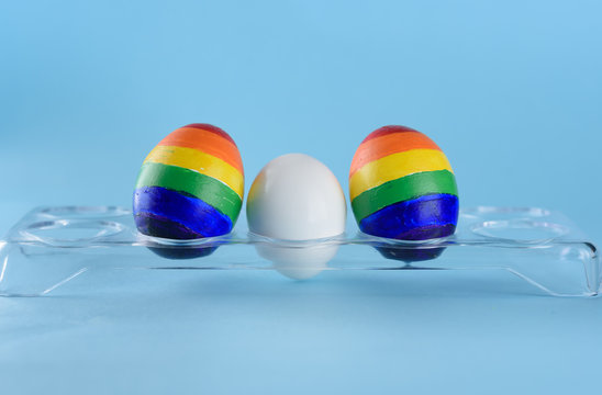 Lgbt family. Eggs with lgbt flag color and white baby egg on blue background. Creative idea for illustration surrogacy law, right homosexual couple adoption and raising a child..