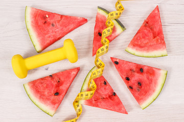Portion of watermelon, dumbbells and tape measure, healthy dessert, sporty lifestyles and slimming concept