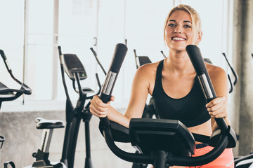 Attractive young woman working out on exercise bike at the gym.