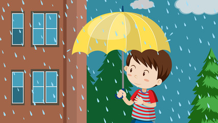 Young boy with umbrella walking in rain