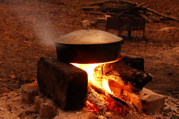Cooking food in cast-iron pan on a bonfire near to campsite at nighttime.