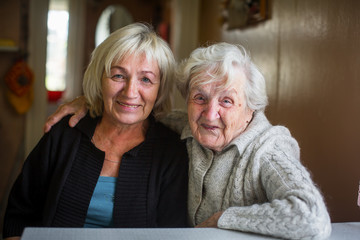 Portrait of an elderly woman with her adult daughter.