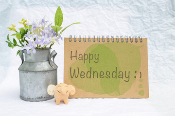 Happy Wednesday on design notebook cover with smiling elephant clay doll and flower pot over blurred background, greeting card concept