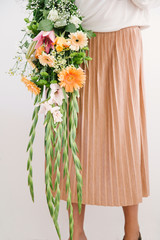 Woman in pinkish beige pleated skirt holds a muted orange themed summer bouquet.