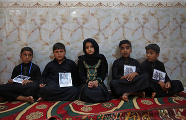 Children hold pictures of their fathers, who were killed by Islamic State militants at Kirkuk road, in Kerbala
