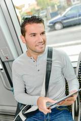 Man on public transport holding tablet