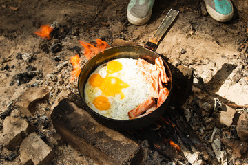 Scrambled eggs with bacon on the cast-iron pan on a bonfire, top view.