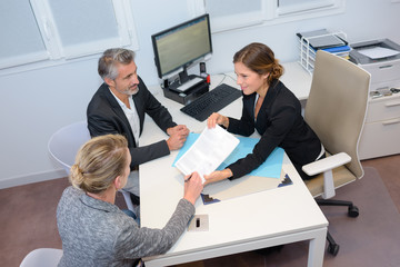 Three people in meeting around office desk
