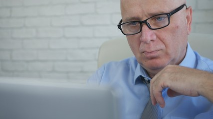 Serious Businessman Thinking and Analyzing Online Laptop Informations