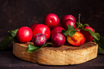 Fresh red plum with leaves on a wooden dark background