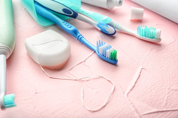 Toothbrushes and dental floss on color background