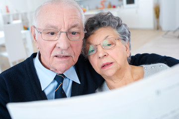 senior couple reading newspaper together at home