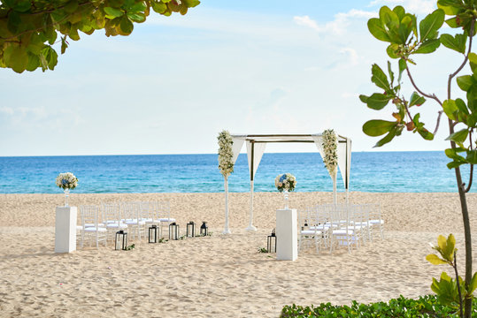 Beautiful beach wedding venue setting with flowers decoration, panoramic ocean view