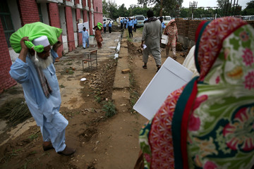 Election officials carry election materials at a distribution centre ahead of general election in Islamabad