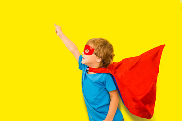 Happy child in Superhero costume playing on a yellow background.