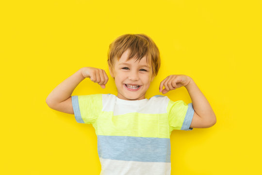 Cute smiling sport child boy showing his biceps on a yellow background.