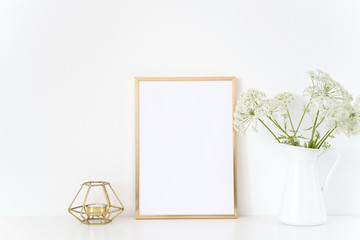 Gold frame mock up with a Aegopodium in jug and candle. Mockup for headline design.Template for lifestyle bloggers,media