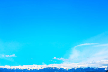 Snow covered mountain peaks and blue sky with clouds background