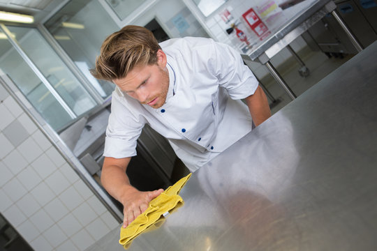 male chef cleaning stainless steel kitchen work surface