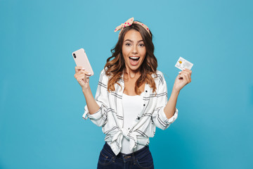 Image of emotional caucasian girl 20s wearing headband laughing while holding smartphone and credit card, isolated over blue background