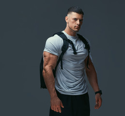 Portrait of a muscular handsome bodybuilder in sportswear with rucksack posing against a gray background.