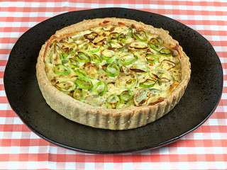Homemade zucchini, leek and ricotta quiche set on a dark plate, on a red tablecloth