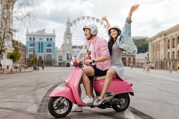 Funny ride. Joyful charming man conducting motorbike and woman putting hands up