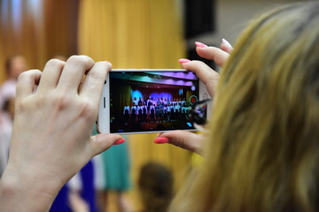 A woman shoots her child's performance at a concert on a smartphone. Her nails are painted pink.  Video will be remembered for her daughter