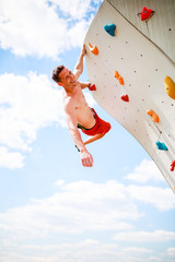 Photo of smiling athlete looking at camera practicing on wall for rock climbing against blue sky with clouds
