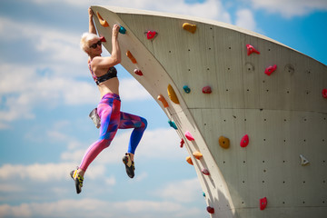 Photo from side of sports girl in leggings hanging on wall for climbing against blue sky