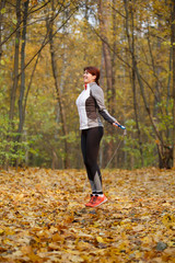 Full-length picture of athlete girl jumping with rope at autumn forest