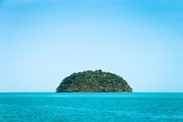 Round green island. Seascape with rock island in the tropical sea, Thailand. Blue clear sky.