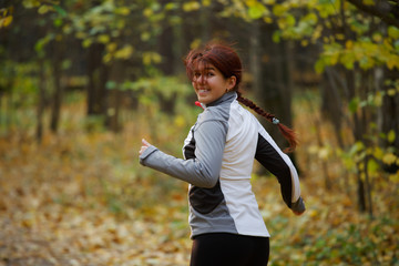 Portrait of happy woman in sportswear on run in autumn