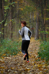 Photo of brunette in sportswear on run in autumn afternoon