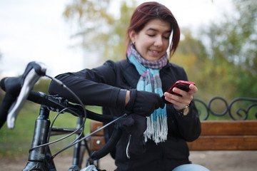 Photo of smiling woman looking in phone sitting on bench